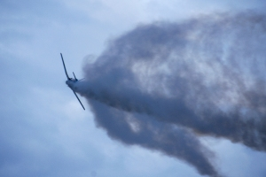 Flying plane with smoke behind it