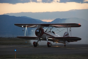 biplane on the runway with a sunset mountain backdrop