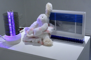 A lamp, photo frame, and stuffed rabbit sit on top of an Ikea computer cabinet.