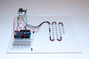 An Arduino micro-controller, breadboard,  strip LEDs,  a barrel plug power adapter, and Ping sensor connections are mounted on a clear acrylic panel.