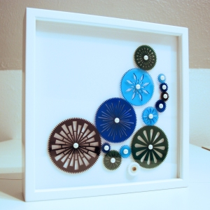 A white frame has fourteen acrylic gears in it. A motor on the back turns the gears.