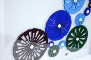 This closeup image of the gears shows the burgundy, green, dark blue and light blue transparent acrylic colors.
