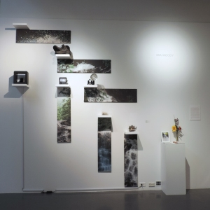 a 10' by 10' art installation of fabric panels, an iPod speaker, white shelves, and flip boxes.